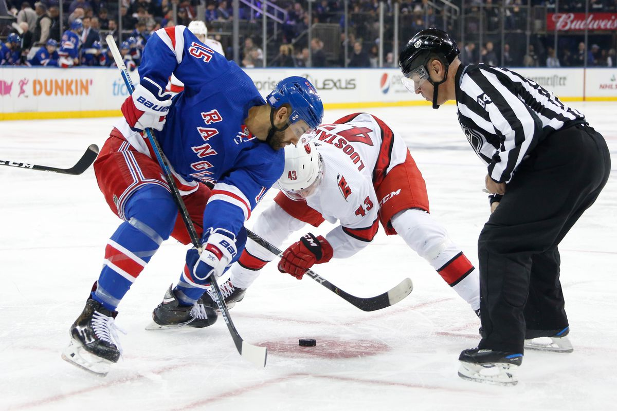 Boo Nieves of the New York Rangers takes a face-off against Eetu Luostarinen of the Carolina Hurricanes at Madison Square Garden on November 27, 2019 in New York City.