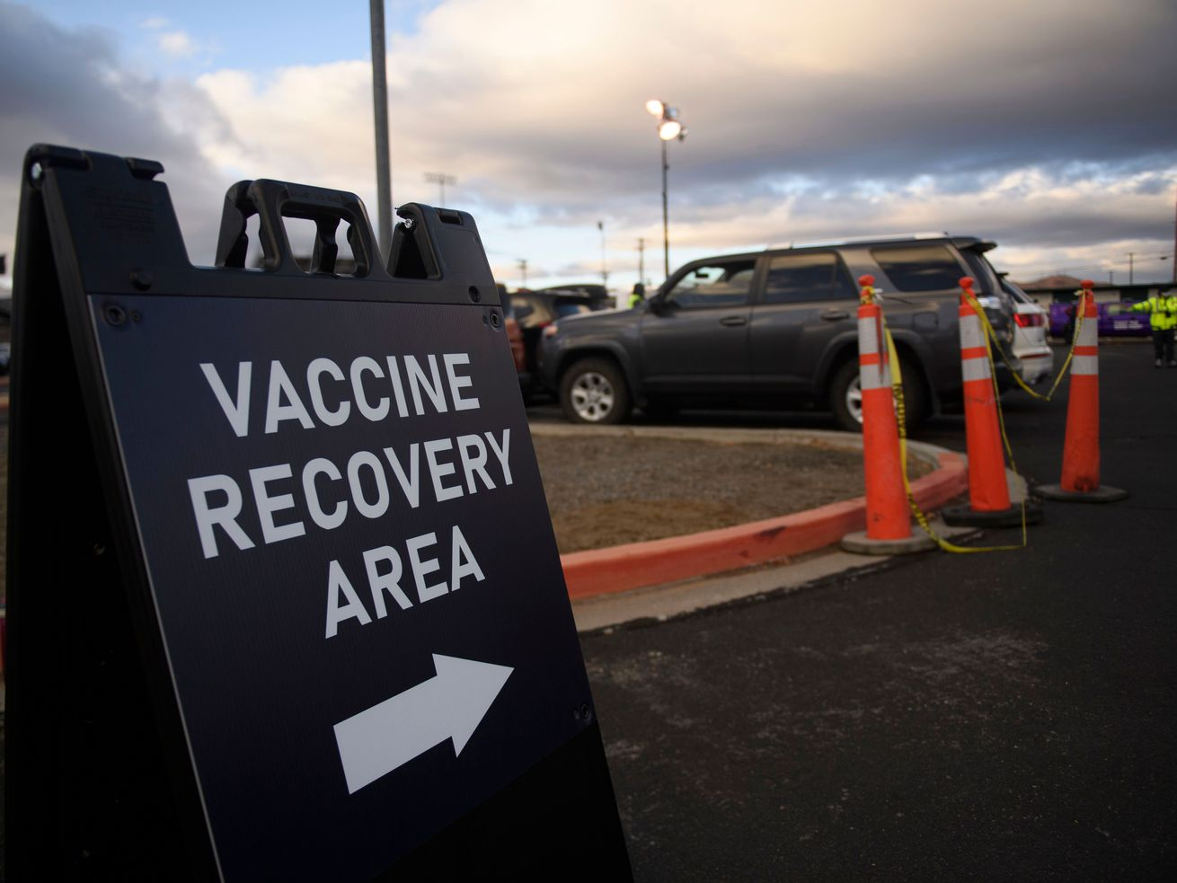"A stand-up sign in a parking lot has an arrow and reads ""vaccine recovery area."""
