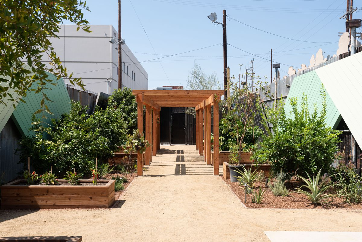 A long, wide look at a small garden space in a funky industrial part of town.