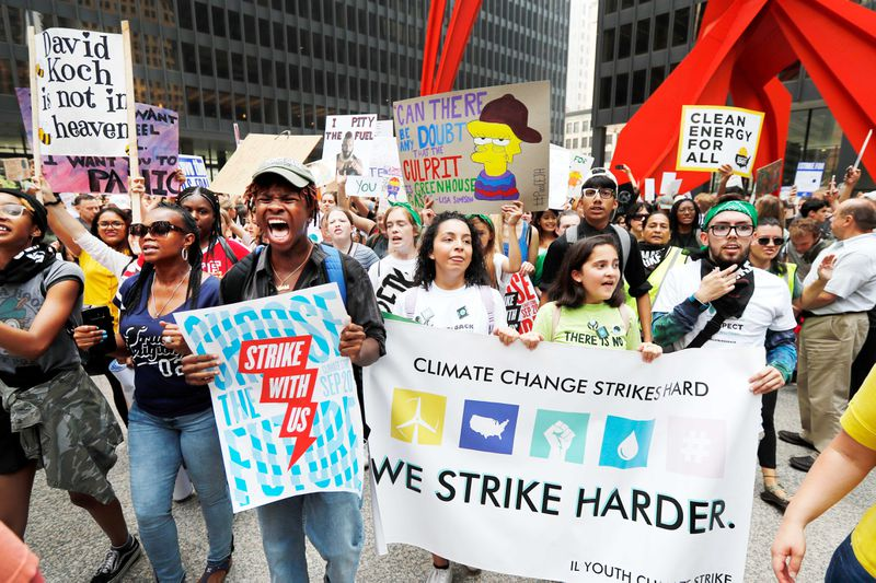 """Protesters for the Global Climate Strike hold signs that read, """"Climate change strikes hard, we stroke harder,"""" and, """"Clean energy for all."""""""