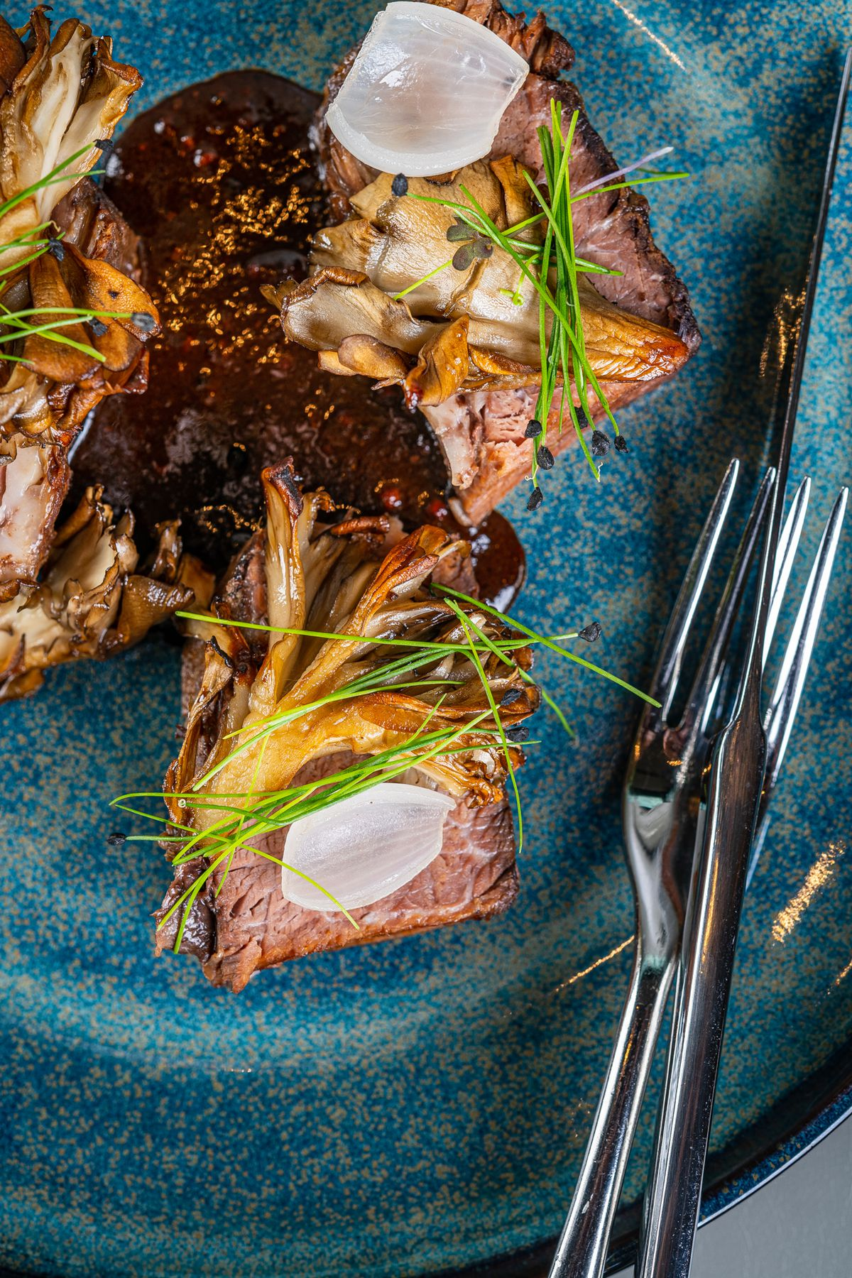 Braised wagyu short ribs come with roasted maitake mushrooms, compressed chives, and cognac-spiked au poivre at Moon Rabbit
