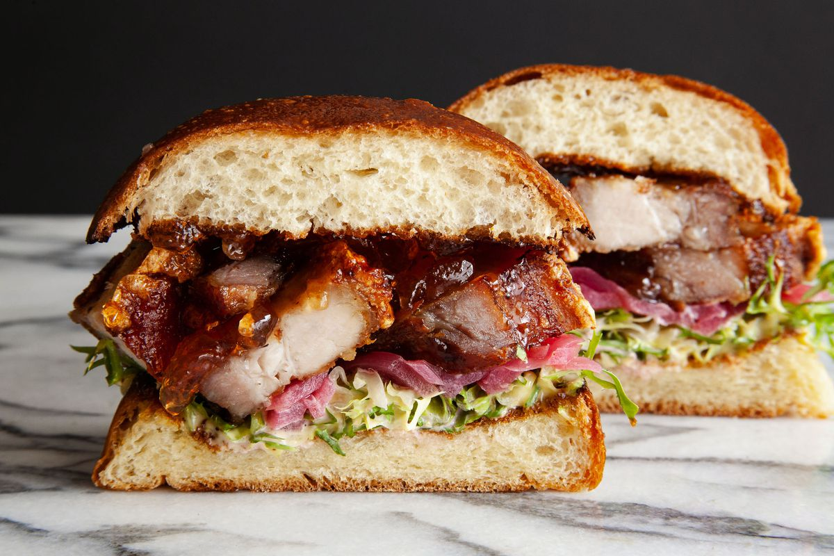 A pork belly sandwich with pepper and pickled onions on challah, cut in half.