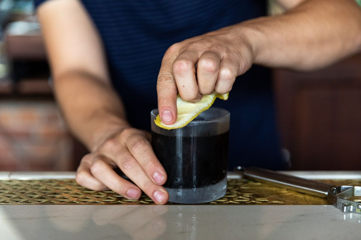 A piece of lemon rind is run across the outer edge of a glass full of brown amaro sour.