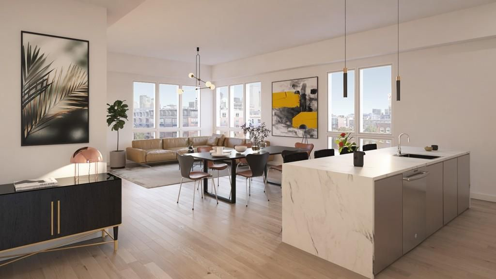 A spacious and modern living room and kitchen area with a large kitchen island.