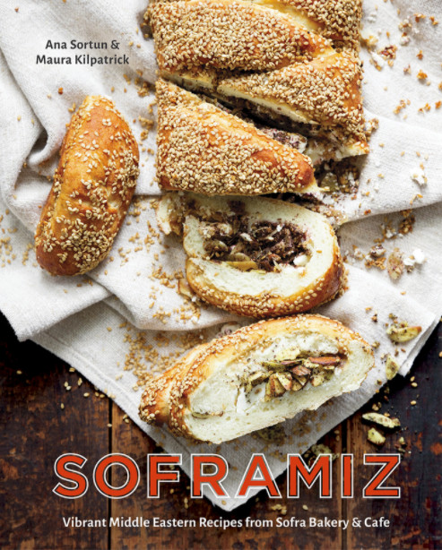 Book cover of Soframiz. A sliced Middle Eastern pastry topped with ample sesame seeds is spread across a cloth napkin on a dark wooden tabletop.