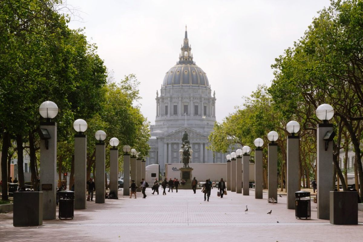 San Francisco City Hall flanked by trees.