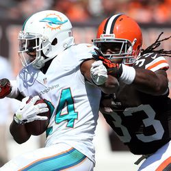 Sep 8, 2013; Cleveland, OH, USA; Miami Dolphins cornerback Dimitri Patterson (24) returns an interception as he his hit by Cleveland Browns running back Trent Richardson (33) during the second quarter at FirstEnergy Field.