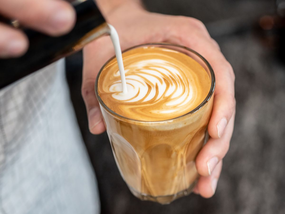 Two hands making latte art inside of a cup.