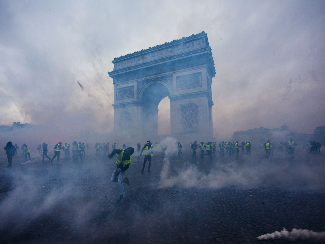 "Tear gas surrounds protesters as they clash with riot police during a ""yellow vest"" demonstration in Paris, France, on December 1, 2018."