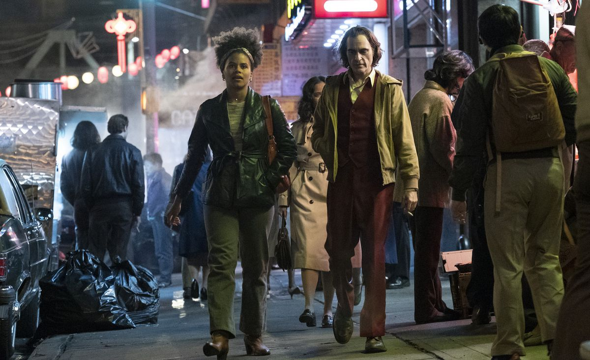 a young black woman and a white man walk down a city street at night in Joker