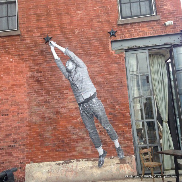 immigrant reaching for star street art