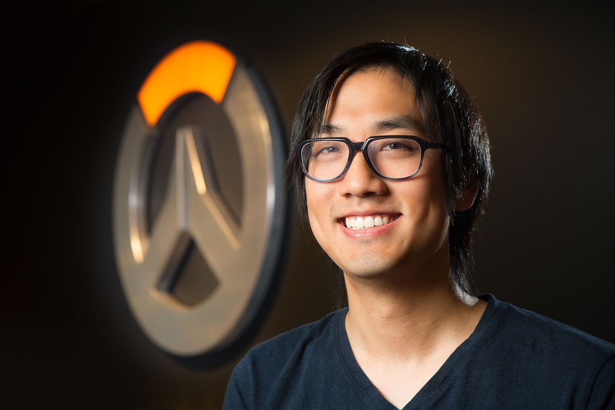 A photograph of Michael Chu in front of the Overwatch logo