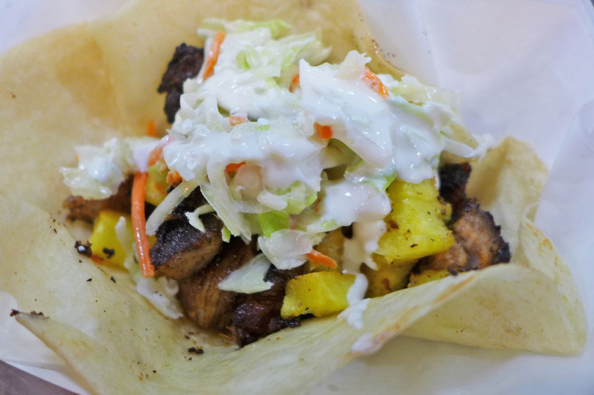 A corn tortilla is heaped with jerk pork, slaw, and crema