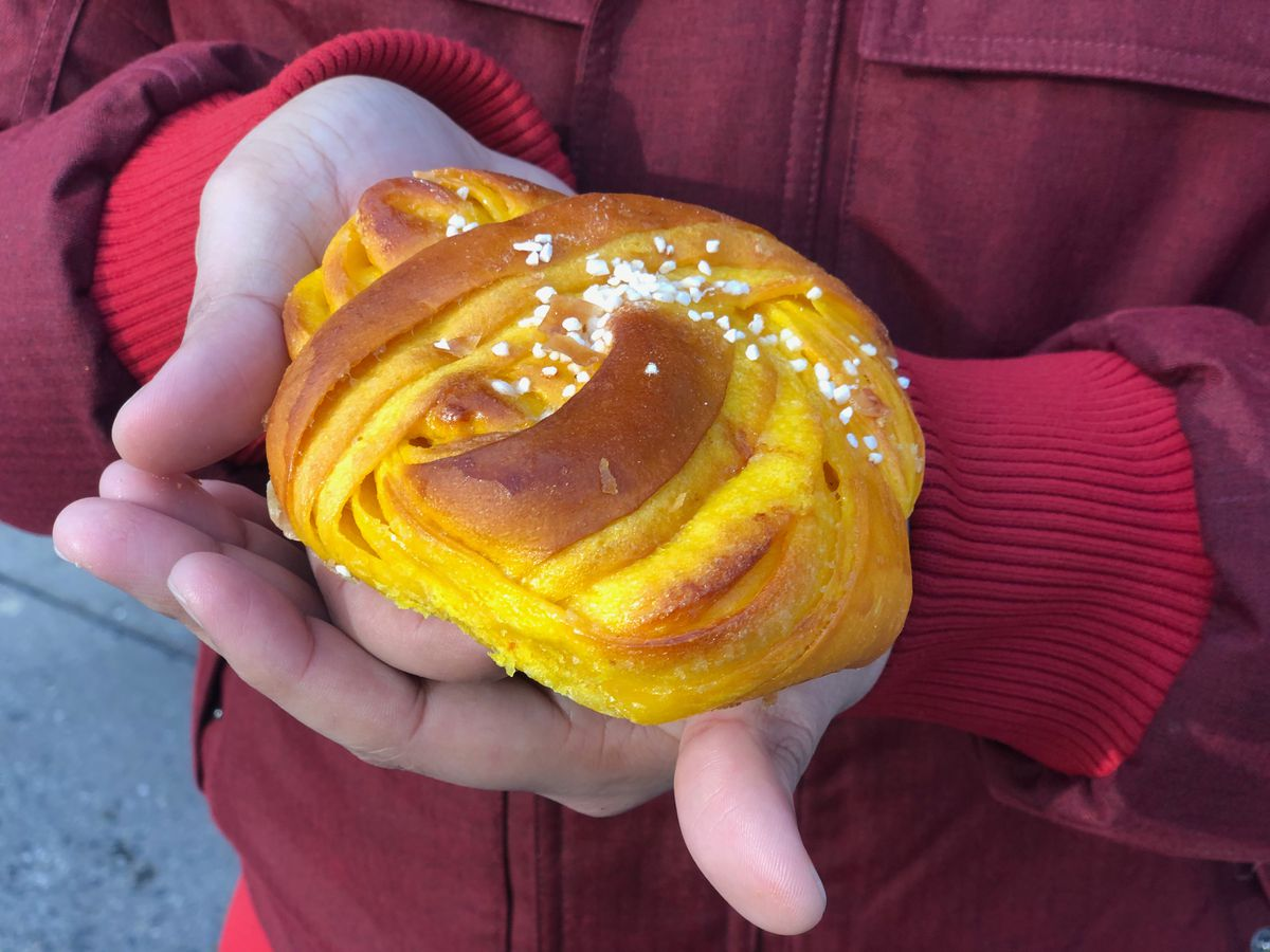 A yellow, swirled saffron bun with a sprinkling of white seeds on top at Fabrique