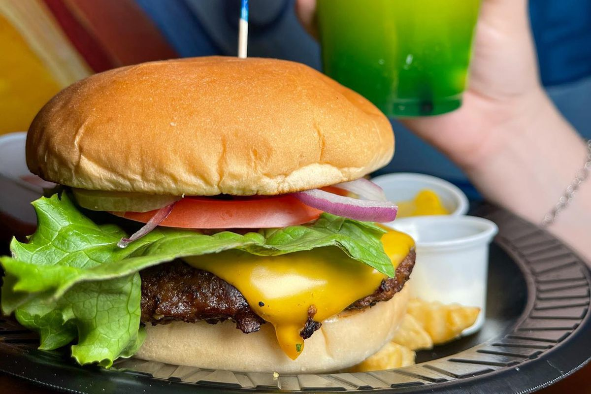 a cheeseburger and a hand holding a neon green drink