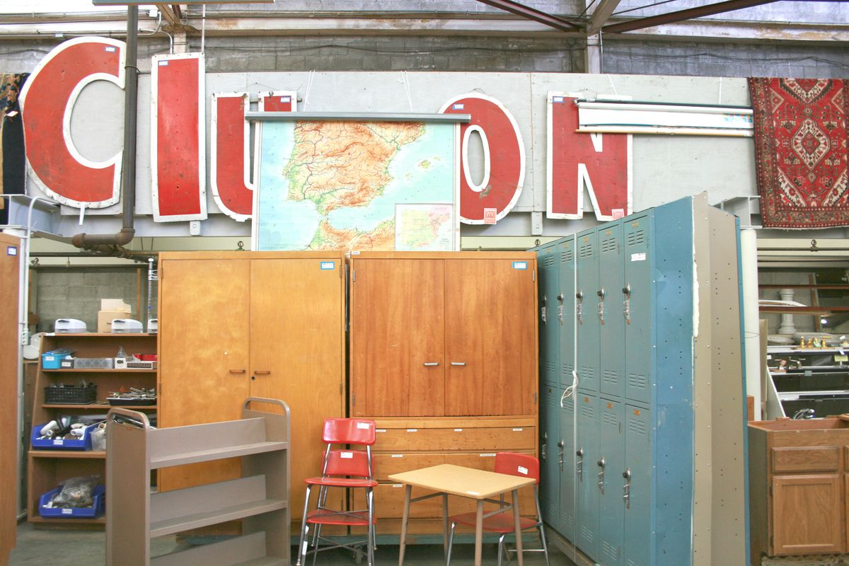 "A variety of furniture objects under a series of standalone red letters, partially obscured by a map, but read ""Clu"" on one side and ""ON"" on the other."