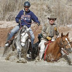 Amy Donaldson and Russ Pack take their horses across the San Rafael River. The riding caters more to the curious, determined and independent.