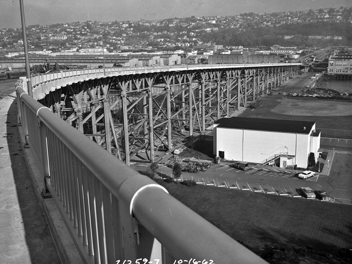 A bridge railing curves around, with wooden bridge supports below. Industrial buildings are in the distance to the left, and one small building is clearly visible to the right.