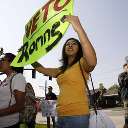 Silvia Salguero joins in as a coalition of activists protests outside the Grand America Hotel in Salt Lake City while Mitt Romney visits, Tuesday, Sept. 18, 2012.