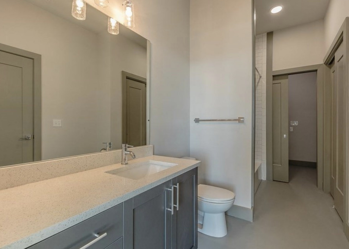 Bathroom with large vanity with one sink, toilet, and large mirror.