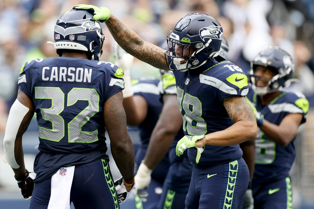 Running back Chris Carson #32 of the Seattle Seahawks celebrates his second quarter touchdown with wide receiver Freddie Swain #18 in the game against the Tennessee Titans at Lumen Field on September 19, 2021 in Seattle, Washington.