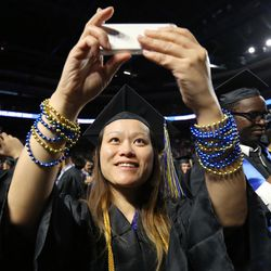 Jus Hu takes a photo after Salt Lake Community College's commencement ceremony at the Maverik Center in West Valley City on Friday, May 6, 2016.