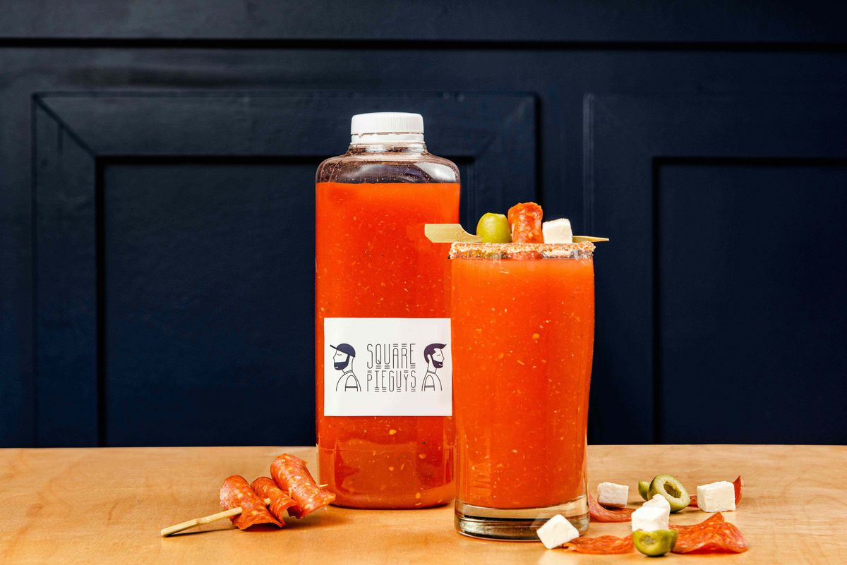 A bottle of Square Pie Guy's take on a bloody mary; the glass is garnished with pepperoni, mozzarella, and green olive