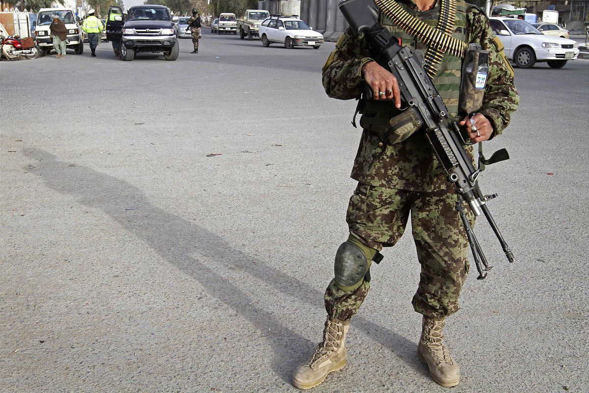 An Afghan soldier stands guard at a checkpoint following Sunday's killing of civilians by a U.S. soldier in Kandahar province, south of Kabul, Afghanistan, Monday, March 12, 2012.