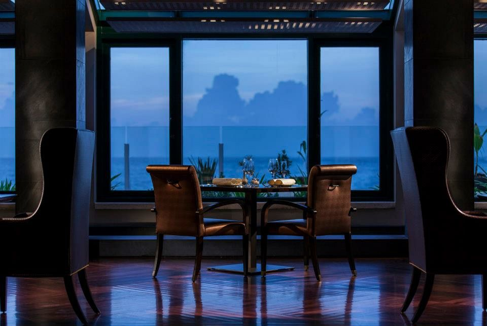 An empty table in a dining room, with a view beyond into a darkened sky and sea