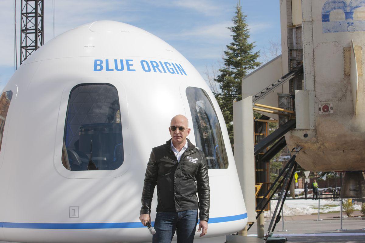 "Jeff Bezos standing beside a space capsule bearing the words ""Blue Origin."""