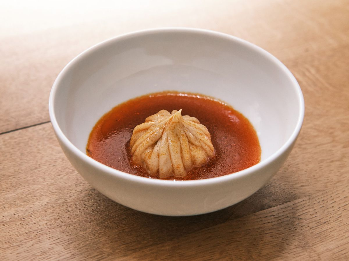 A delicately folded mandu in a bowl of broth on a wooden tabeltop