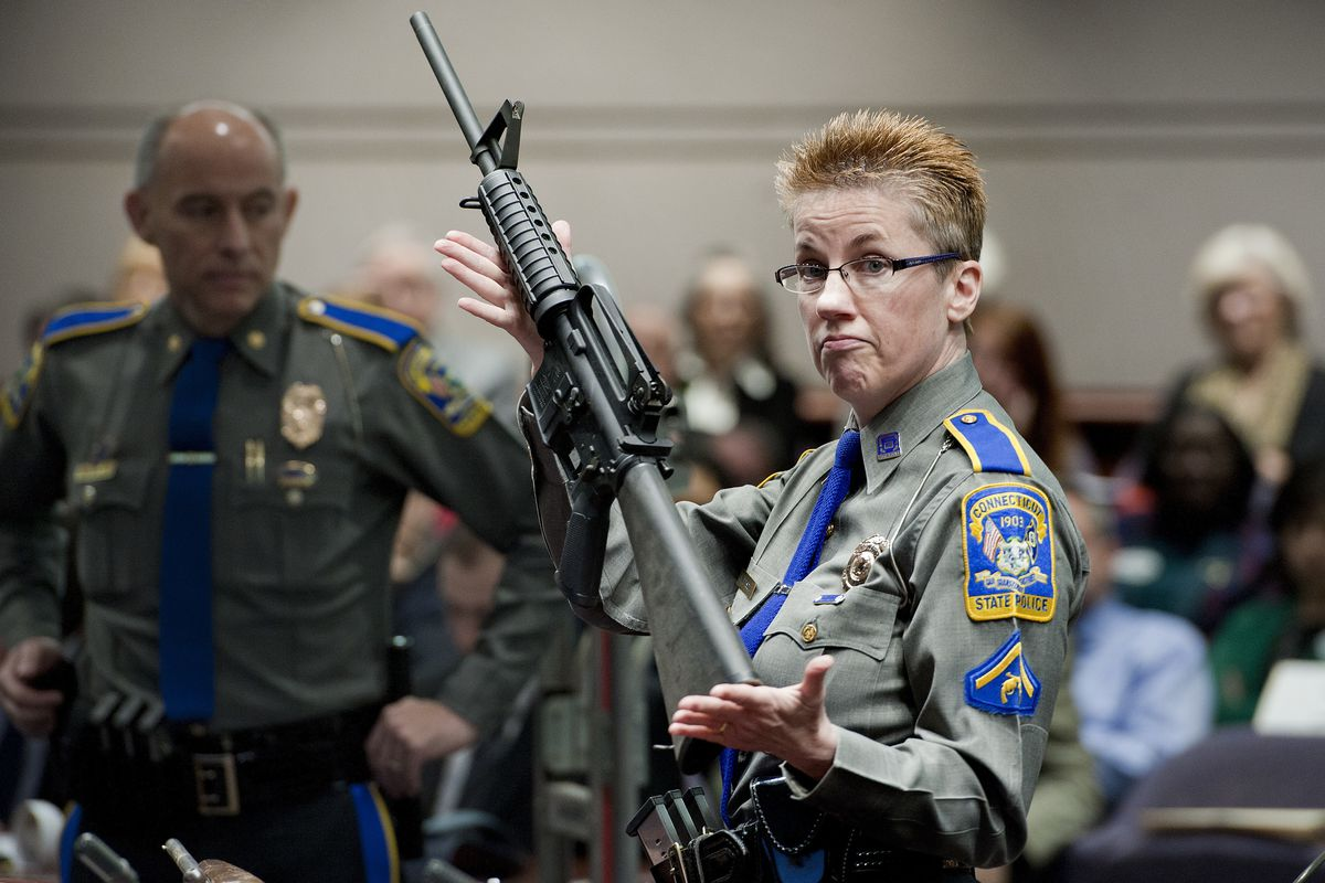 FILE - In this Jan. 28, 2013, file photo, firearms training unit Detective Barbara J. Mattson, of the Connecticut State Police, holds a Bushmaster AR-15 rifle, the same make and model used by Adam Lanza in the 2012 Sandy Hook School shooting, during a hea