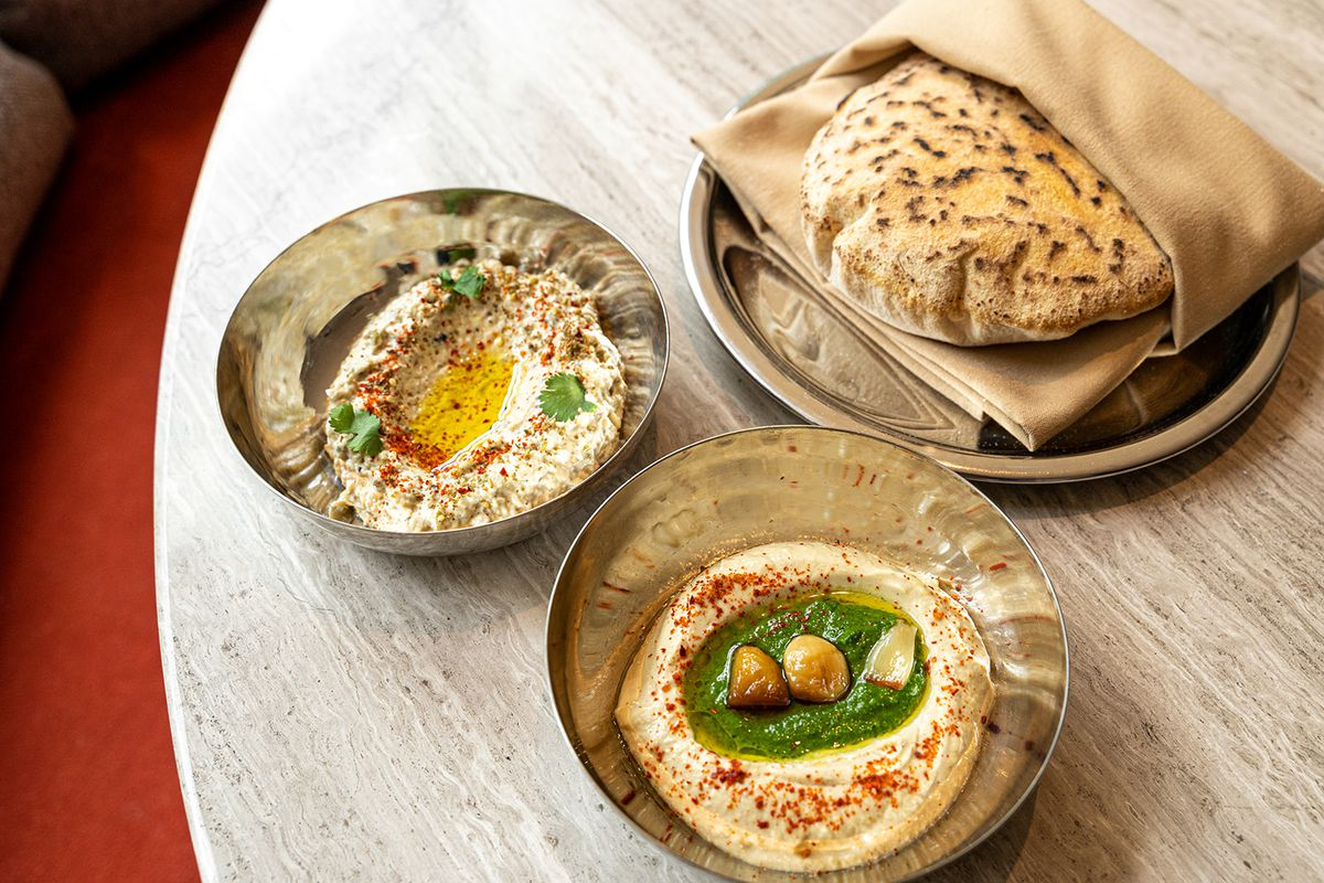 Silver bowls of hummus and baba ghanoush served with kamut pita sit on a grey wood table.