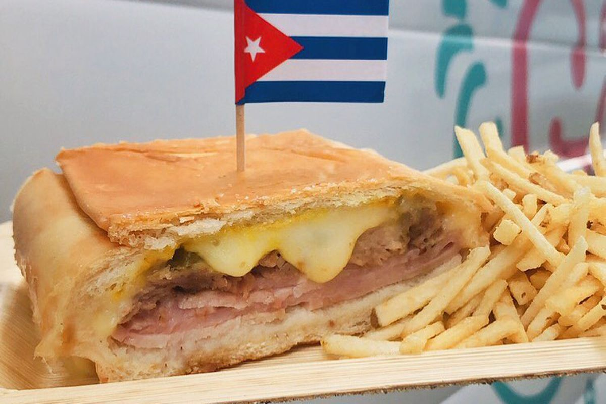 A Cuban sandwich with a Cuban flag on top and a side of fries