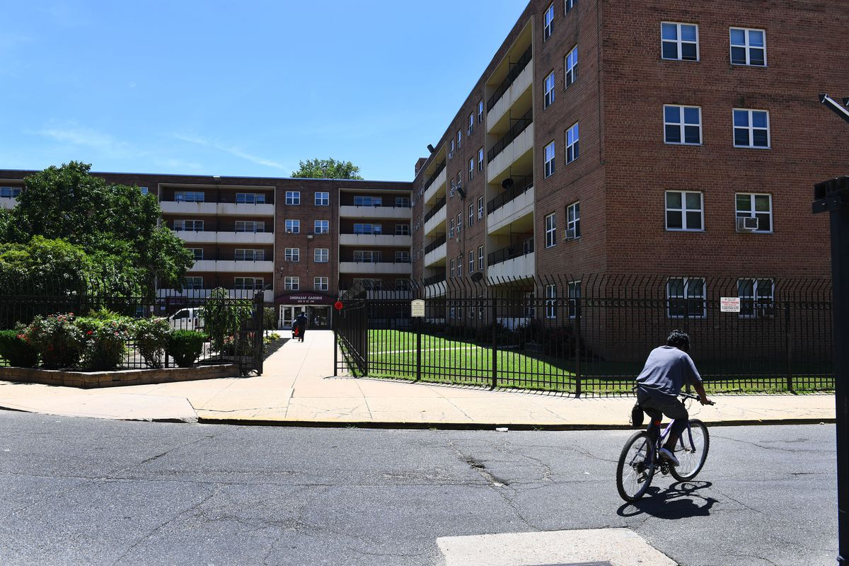 A public housing complex in Washington, D.C. A man rides a bicycle on the street in front of the complex.