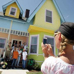 """Kim Davis shoots a photo of her family outside the """"Up"""" home in Herriman, Utah Monday, Aug. 8, 2011."""