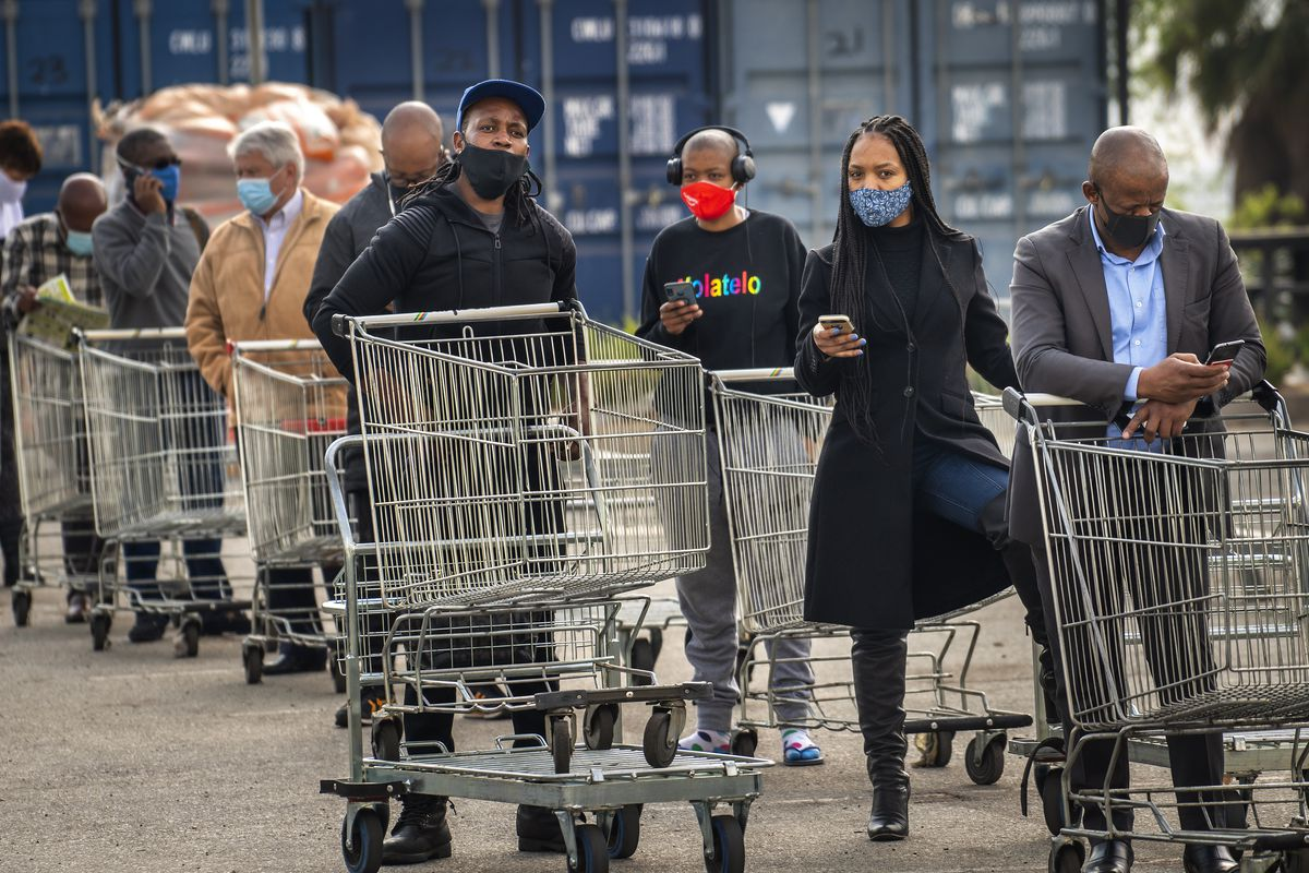 Customers lineup to enter an hyper store in Johannesburg, South Africa, Tuesday, Aug. 18, 2020.