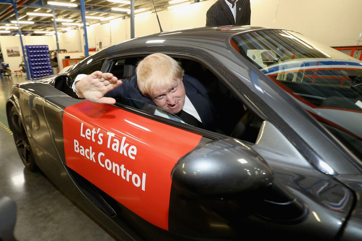 Boris Johnson waves from the driver's seat(!) of a Vote Leave campaign car.