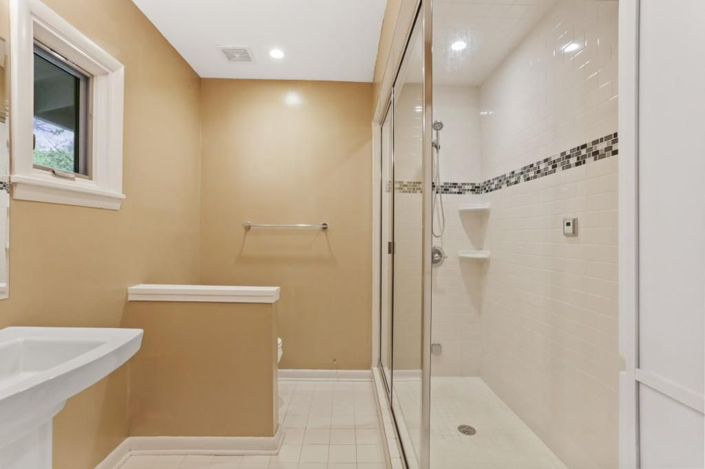 A master Bathroom with yellow walls and a tub.