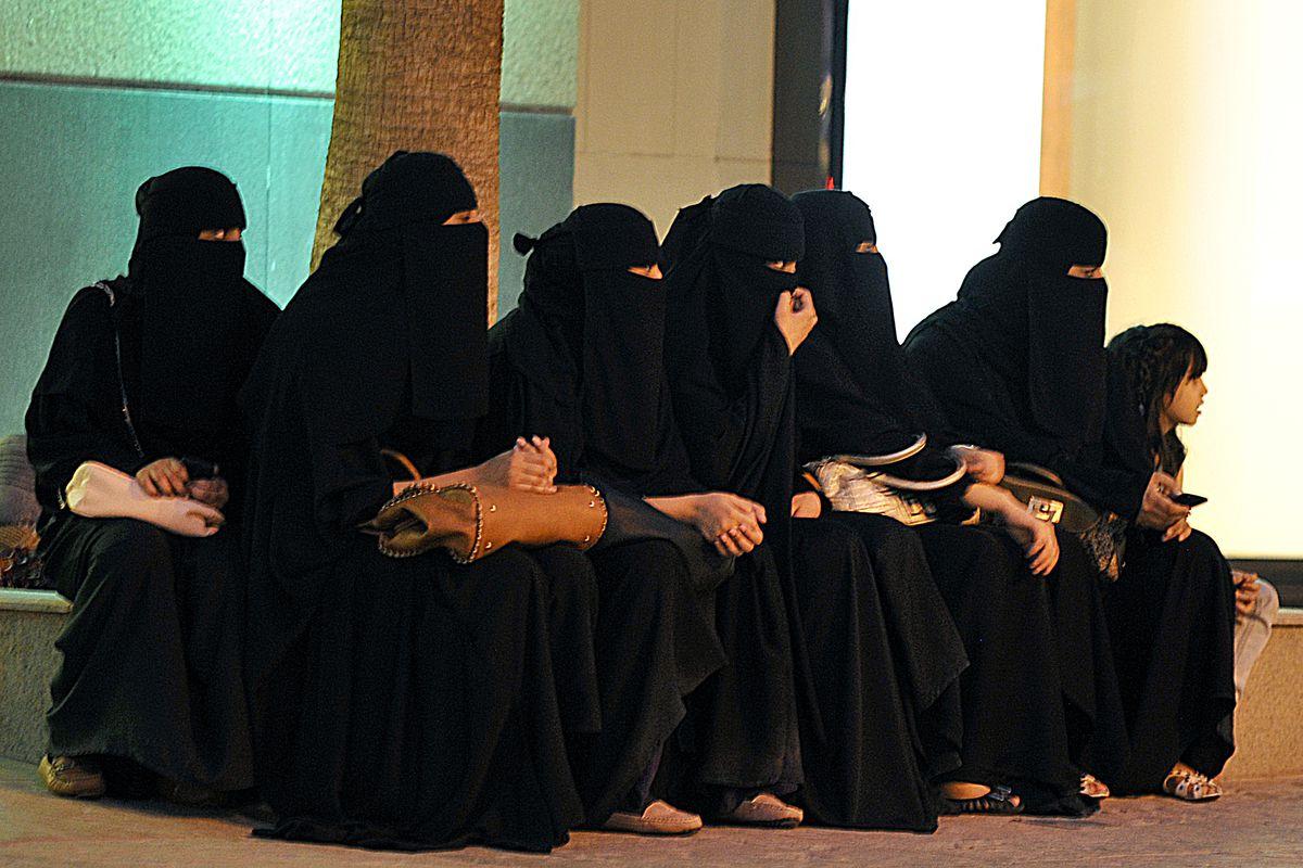 Veiled Saudi women wait for their drivers outside a shopping mall in Riyadh.