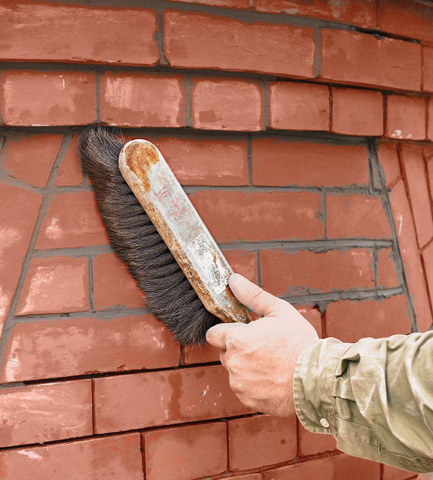 Person brushing brick wall with stiff bristle brush.