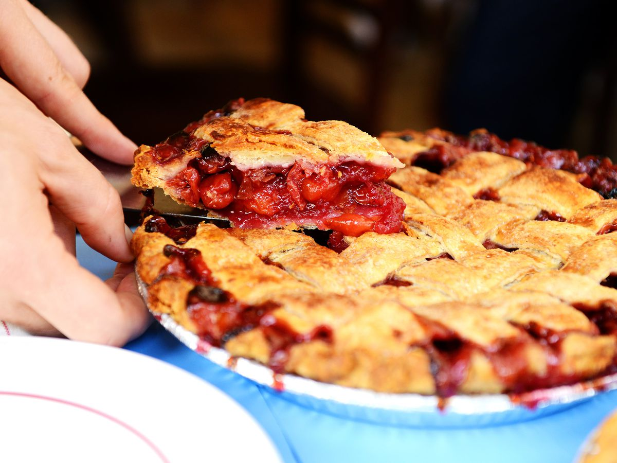 A person cutting out a slice of cherry pie