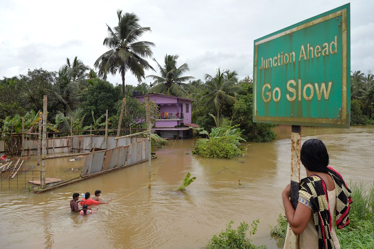 An Indian woman watches residents walking through flood streets next to their marooned houses in the south Indian state of Kerala on August 17, 2018.
