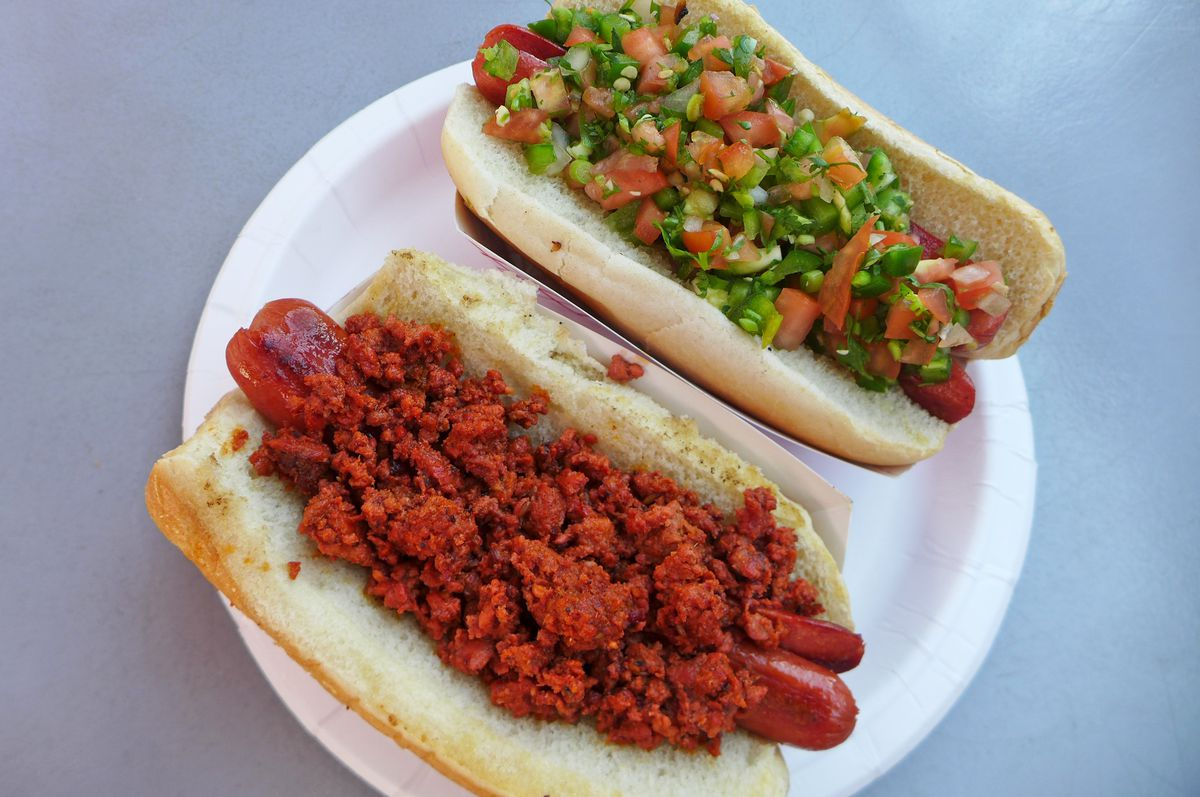 Two hot dogs, one with bright red ground chorizo, the other with minced vegetables