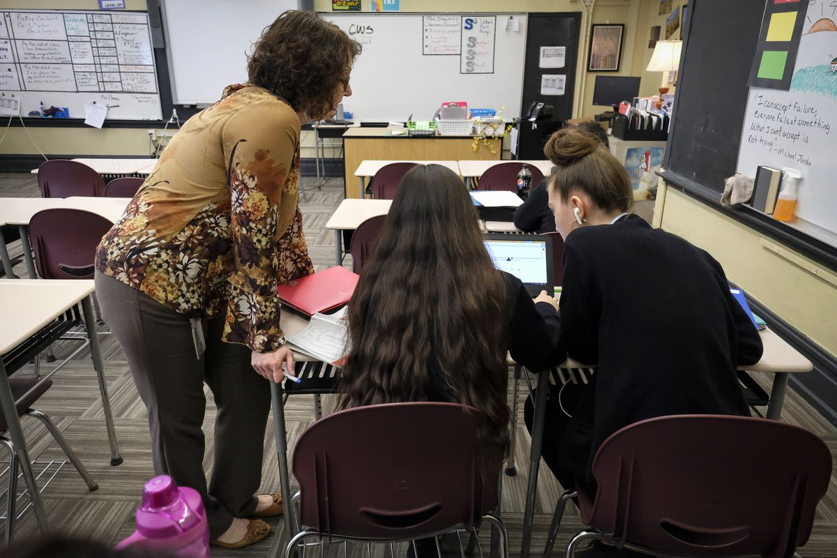 In a classroom, two students work together on a laptop while a teacher looks on.