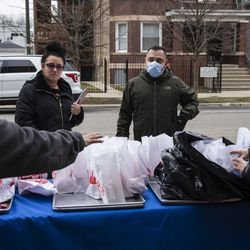 Eileen Rodriguez, 34, and 45-year-old Jaime Funes receive three days of free breakfast and lunch meals for their two students at William P. Nixon Elementary School, 2121 N. Keeler Ave., Thursday morning, March 19, 2020. All Illinois schools, including Chicago Public Schools, are closed for weeks amid fears of the coronavirus pandemic.