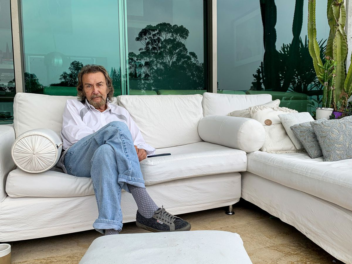 Diego Angel sits outside his house