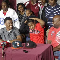 Lowndes High School's Josh Harvey-Clemons, second from left, watches sister Ashley Clemons take off her sweatshirt to unviel a Georgia t-shirt  during a national signing day news conference in Valdosta, Ga., Wednesday, Feb. 1, 2012.  Harvey-Clemons announced his intentions to attend and play football at Georgia.