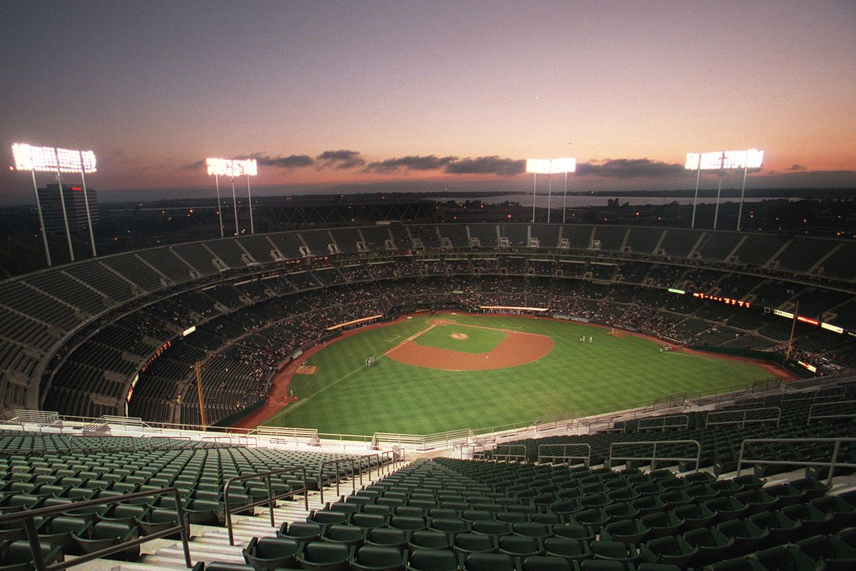"""Is the sun setting on Oakland A's baseball? The football seats on """"Mount Davis"""" loom over the baseball field at Network Associates Coliseum before Friday night's A's game versus the Kansas City Royals, another """"small market"""" team. (Contra Costa Times/Kar"""