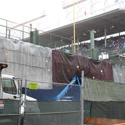 3:16 p.m. Tarps hanging from the back of the left-field bleachers. They were working under there -